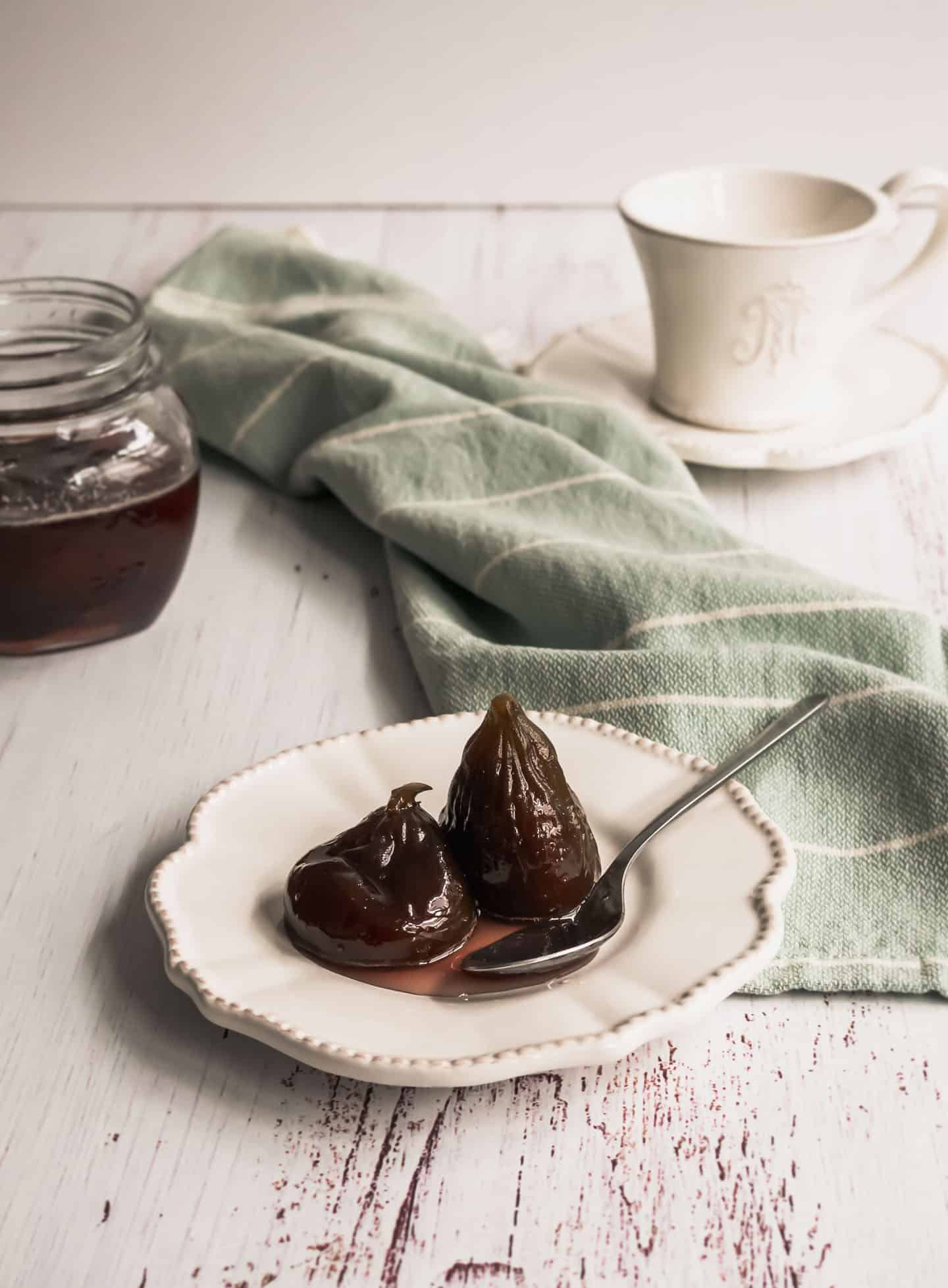 Figs in Syrup in front of a open jar with figs and a tea cup