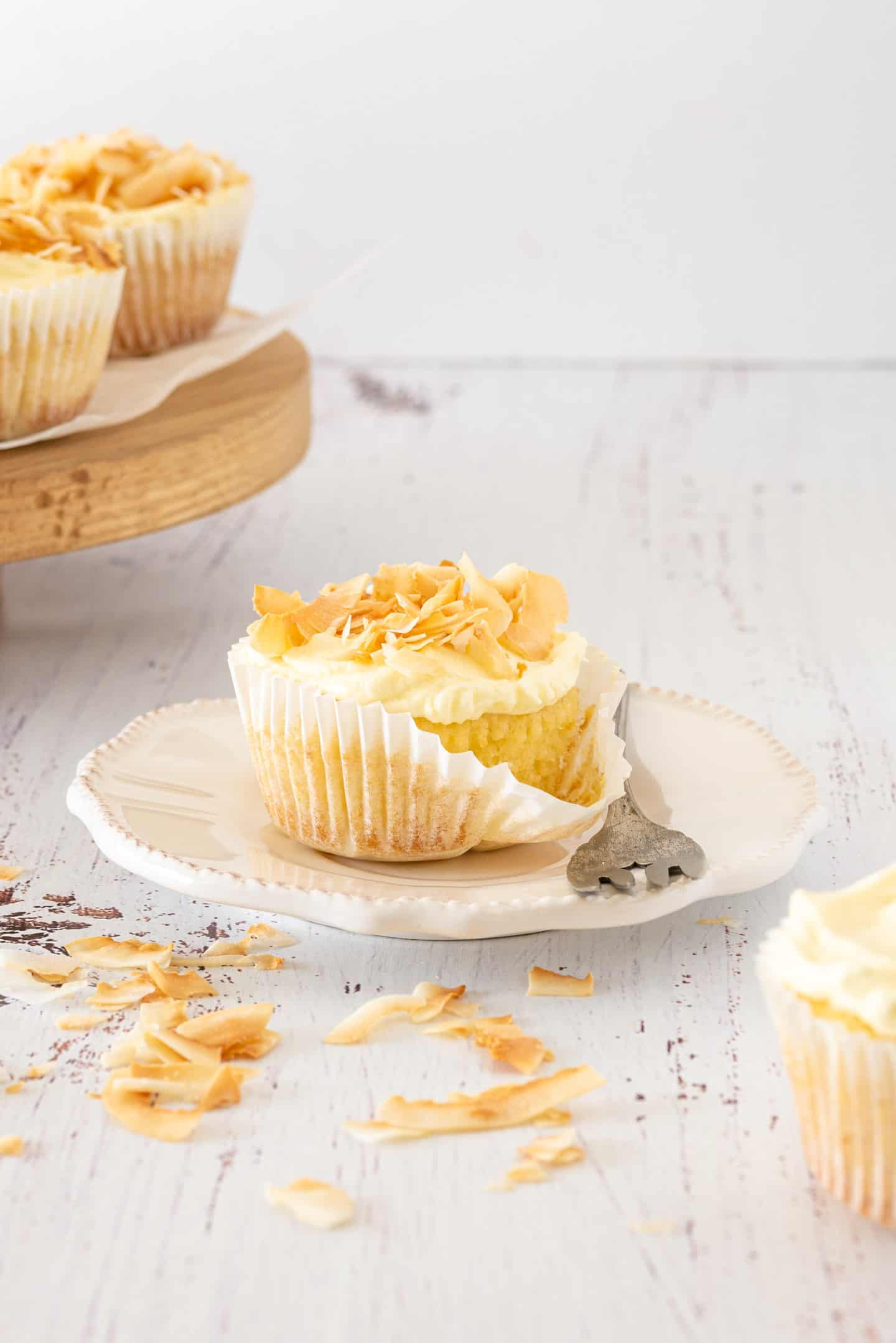 Coconut Tres Leches Cupcakes with a fork and a wooden stand at the background.