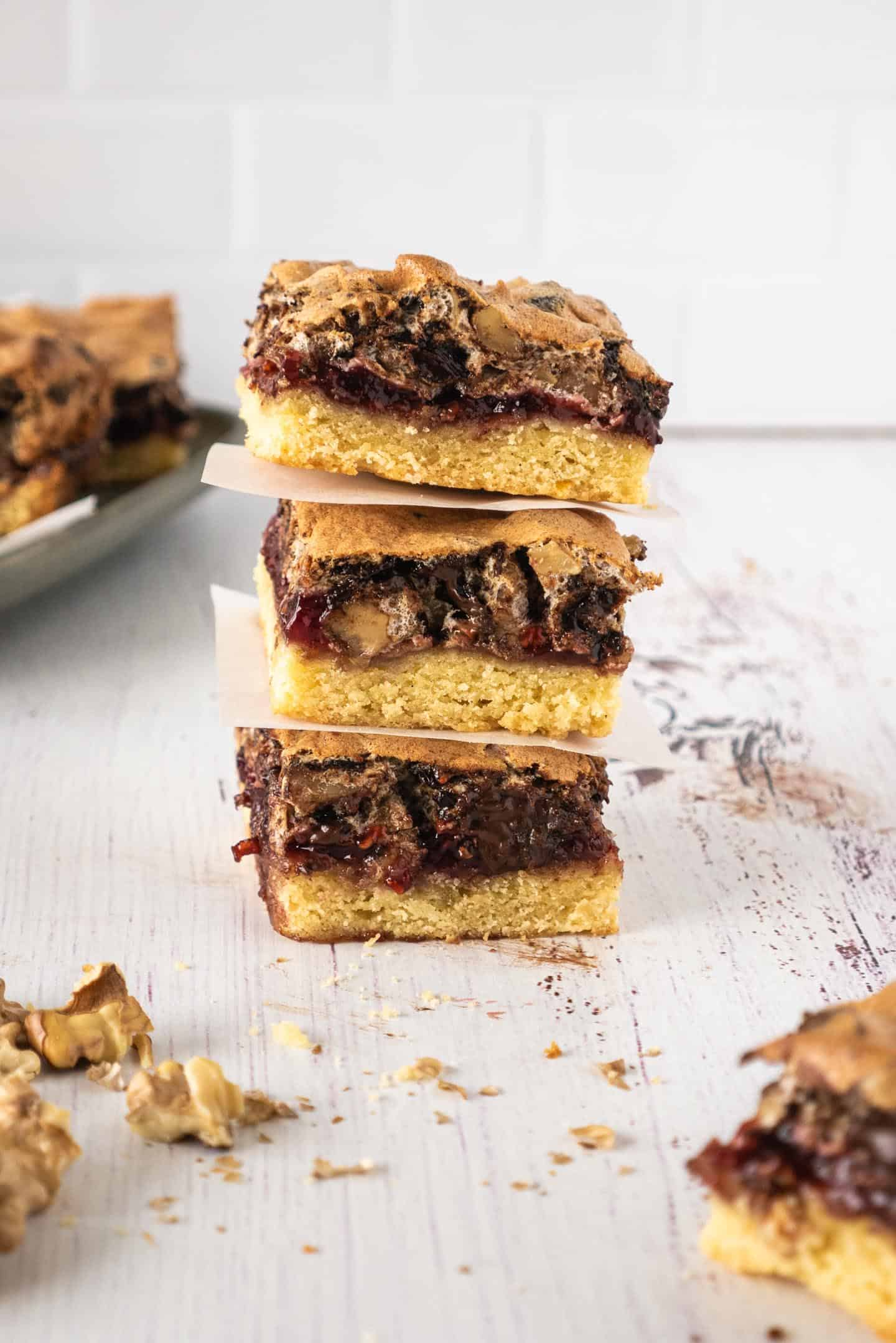 Three square raspberry bars with chocolate and walnuts meringue, and a plate with more tart at the back