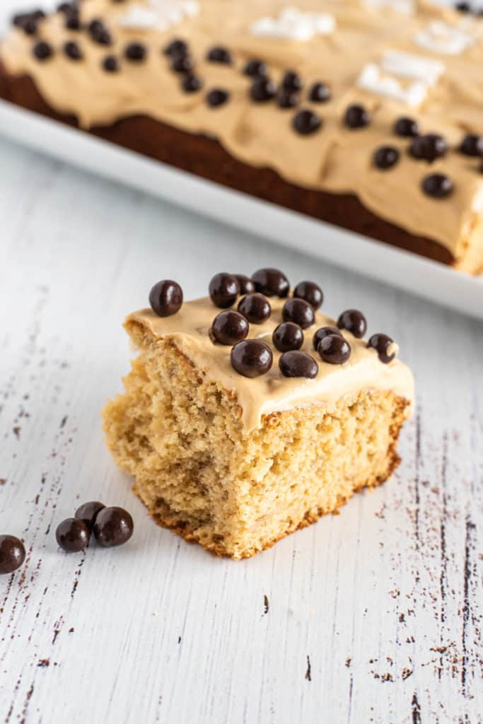 Slice of banana sheet cake with chocolate-covered blueberries