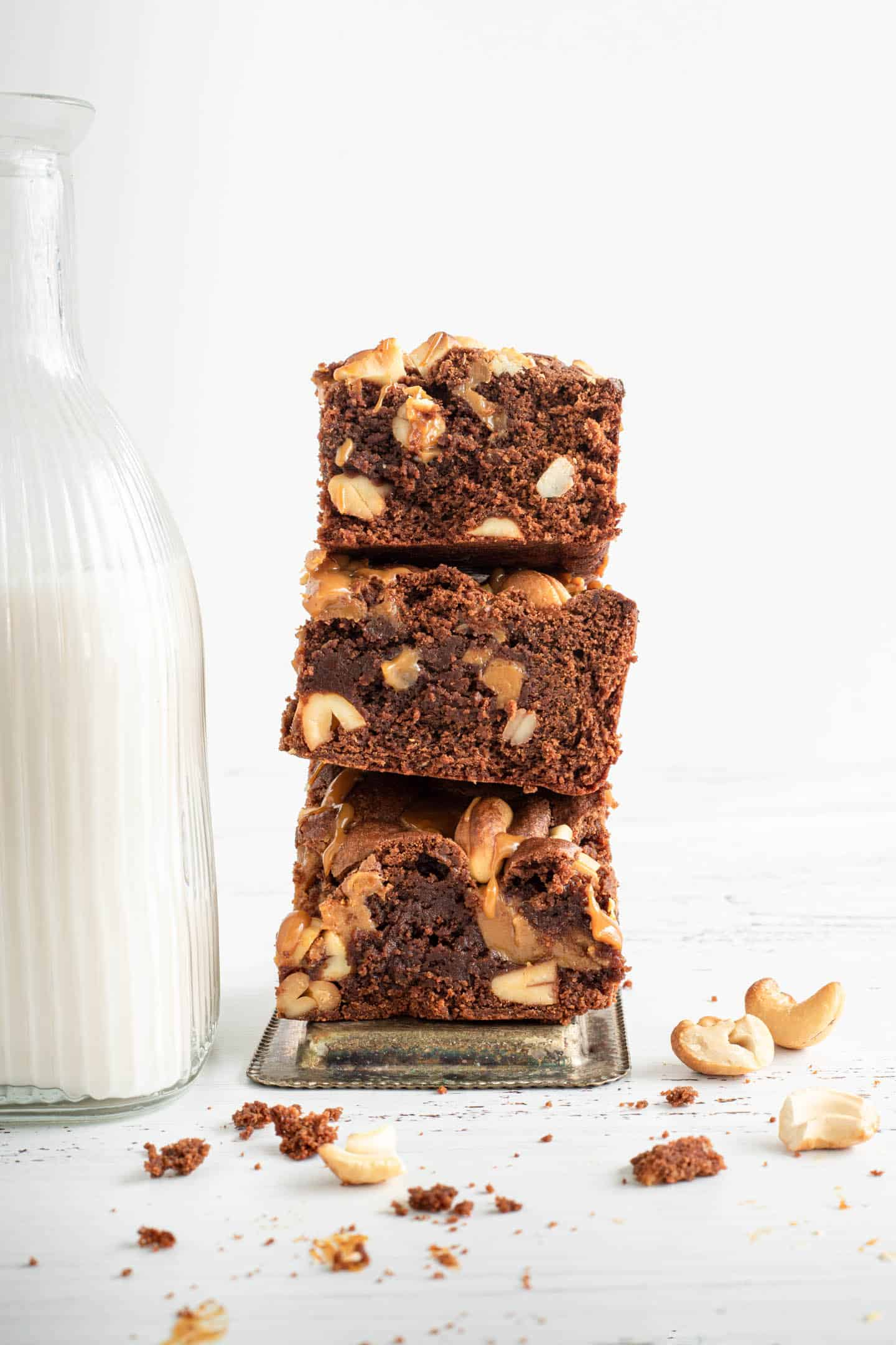 Three squares of dulce de leche brownies piled on the side of a bottle of milk and cashews around