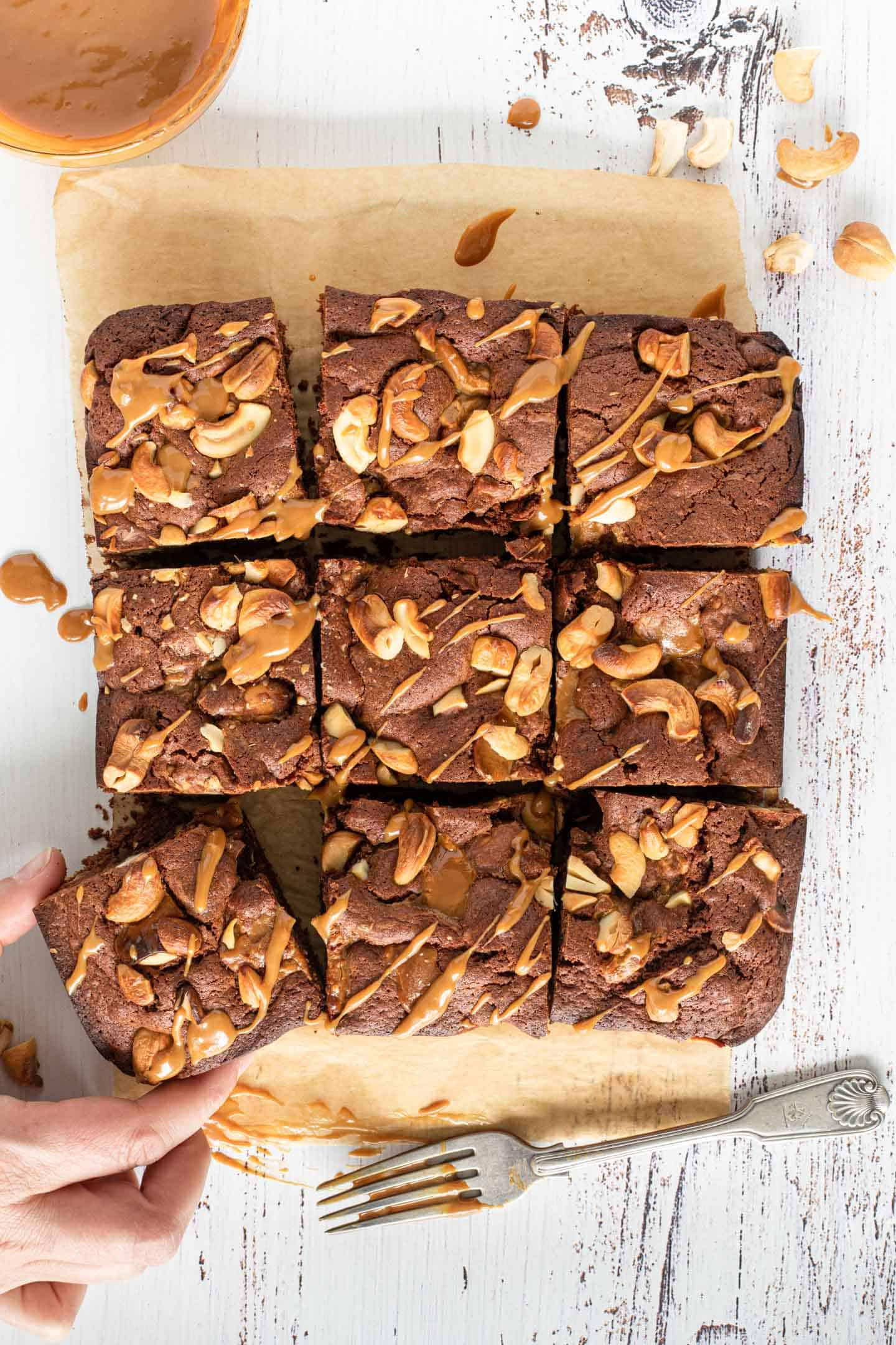 Brownies with cashews and dulce de leche cut into squares on brown parchment paper