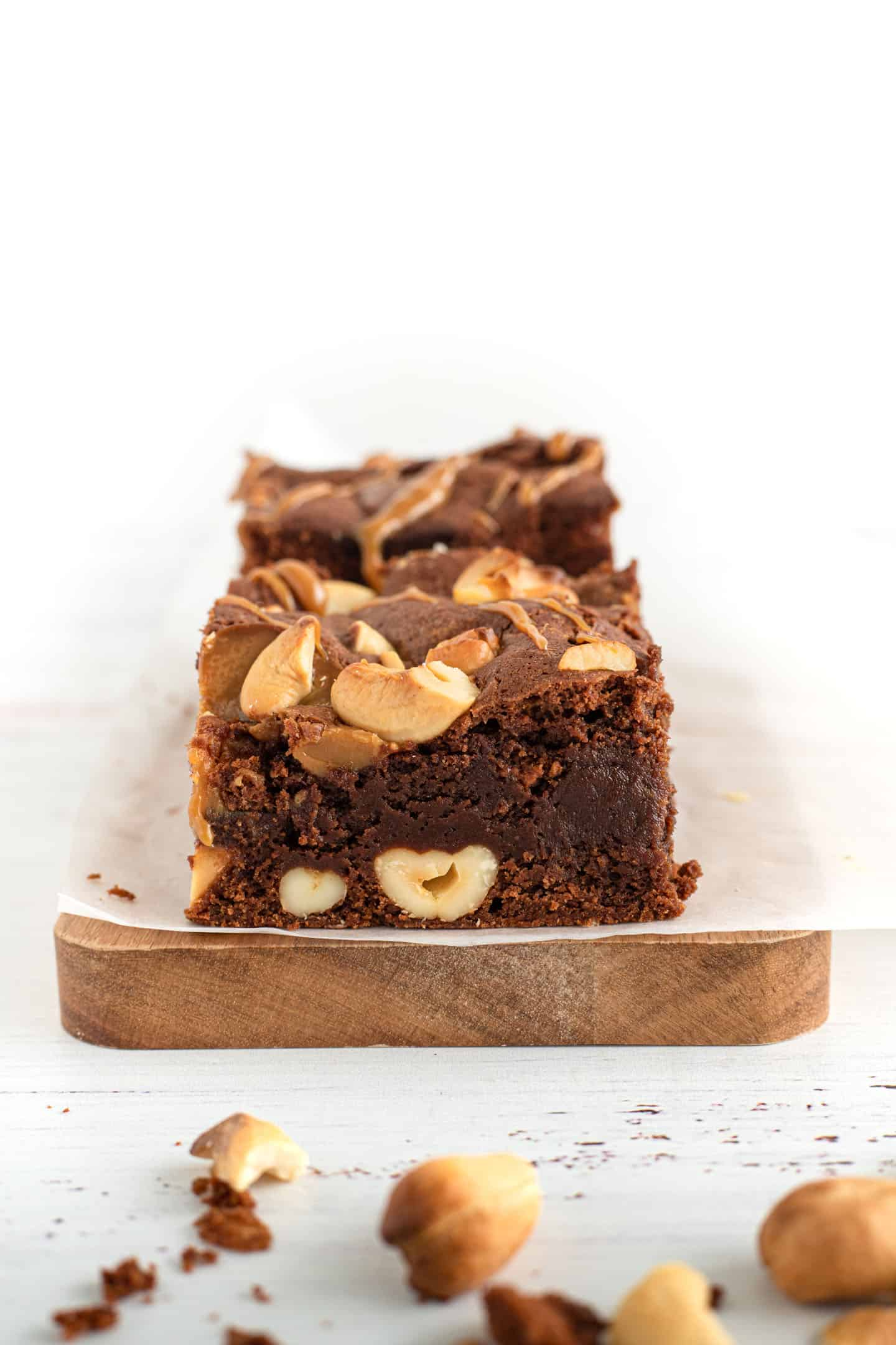 Square of dulce de leche cashews brownie on white parchment paper on a wooden board