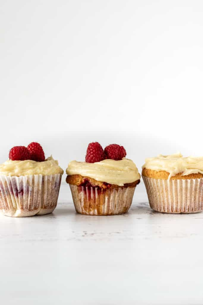 Three cupcakes, two with some raspberries on the buttercream on a white surface and white backdrop