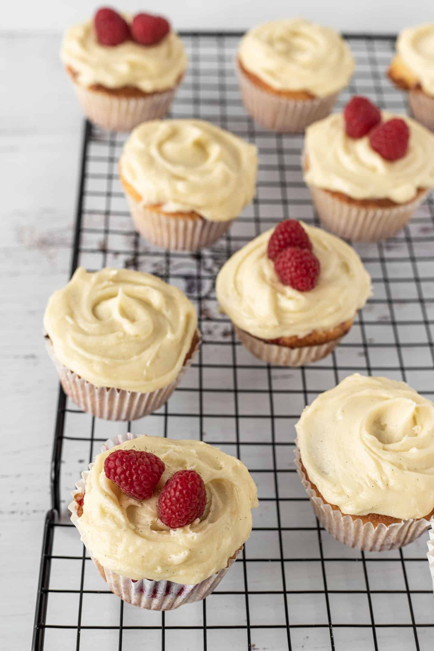 Raspberry and orange cupcakes on a rectangular cooling rack, some with raspberries on top of the buttercream and other without