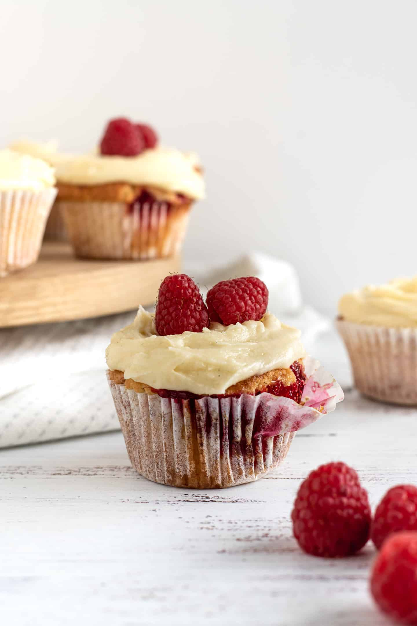 Cupcake with some buttercream and raspberries on top, on a wooden stand at the back