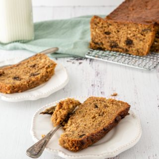 Two slices of prune loaf cake in front of the whole cake on a cooling rack in one corner and a bottle of milk on the other.