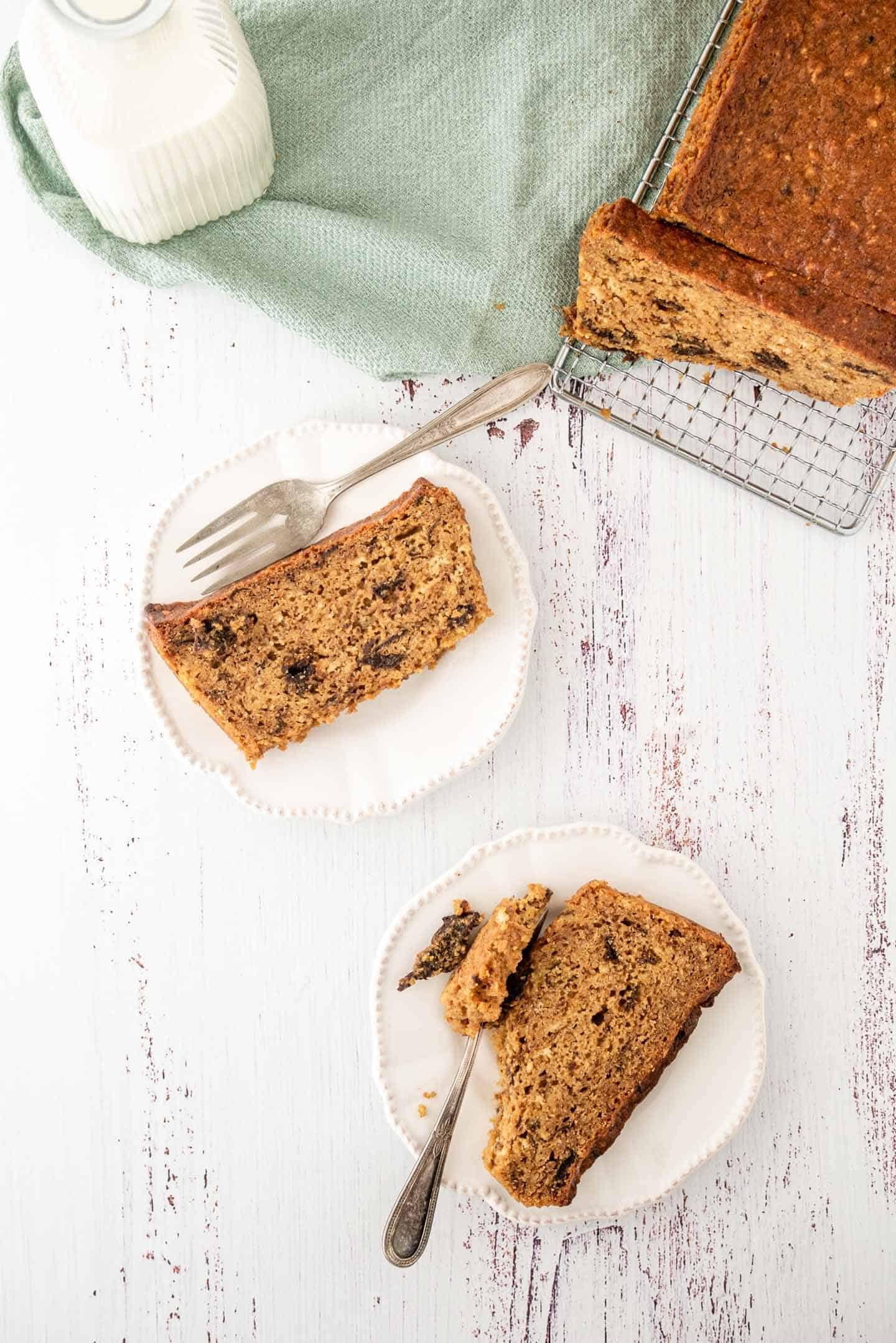 Two slices of cake on white plates, with the whole prune lof cake on a cooling rack in one corner and a green tea towel on the other