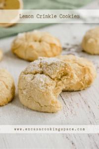 Bitten lemon crinkle cookie on a wooden board