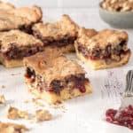 Cuadrados de tarta de frambuesa con merengue de chocolate y nueces, un espátula con mermelada a la dereche y un bol pequeño atrás con nueces