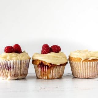 Tres cupcakes, dos con frambuesas sobre la crema de manteca en una superficie blanca y fondo blanco