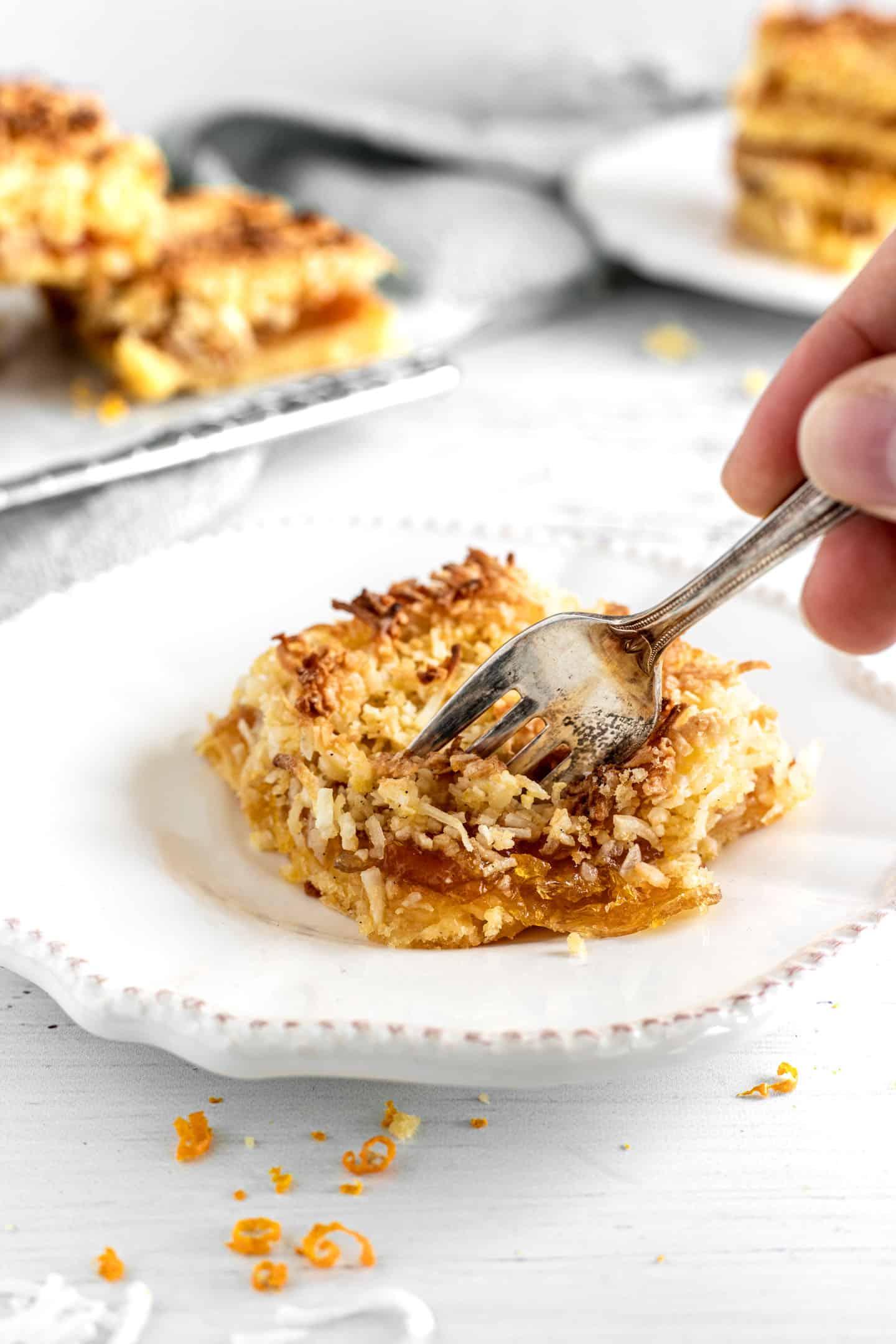 Tenedor cortando un pedazo de un cuadrado de tarta sobre un plato blanco, con una rejilla rectangular por detrás y más tarta por encima.