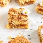 Porciones cuadradas de tarta de naranja y coco con pequeñas margaritas por encima