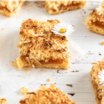 Square bars of coconut and orange marmalade tart with little daisies on top