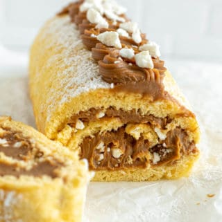 Dulce de leche cake roll on a baking sheet, with a small bowl with dulce de leche behind it