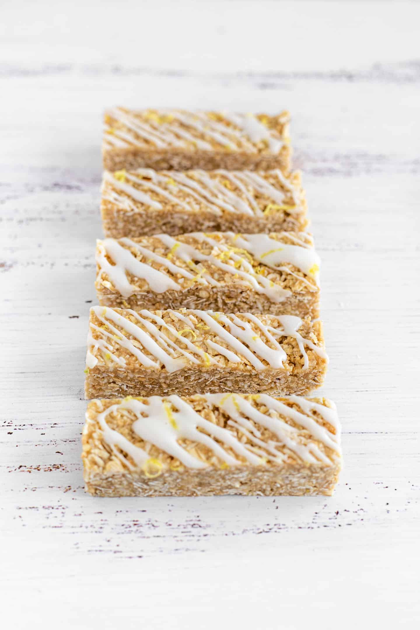 Lemon, coconut and oats bars on a white surface