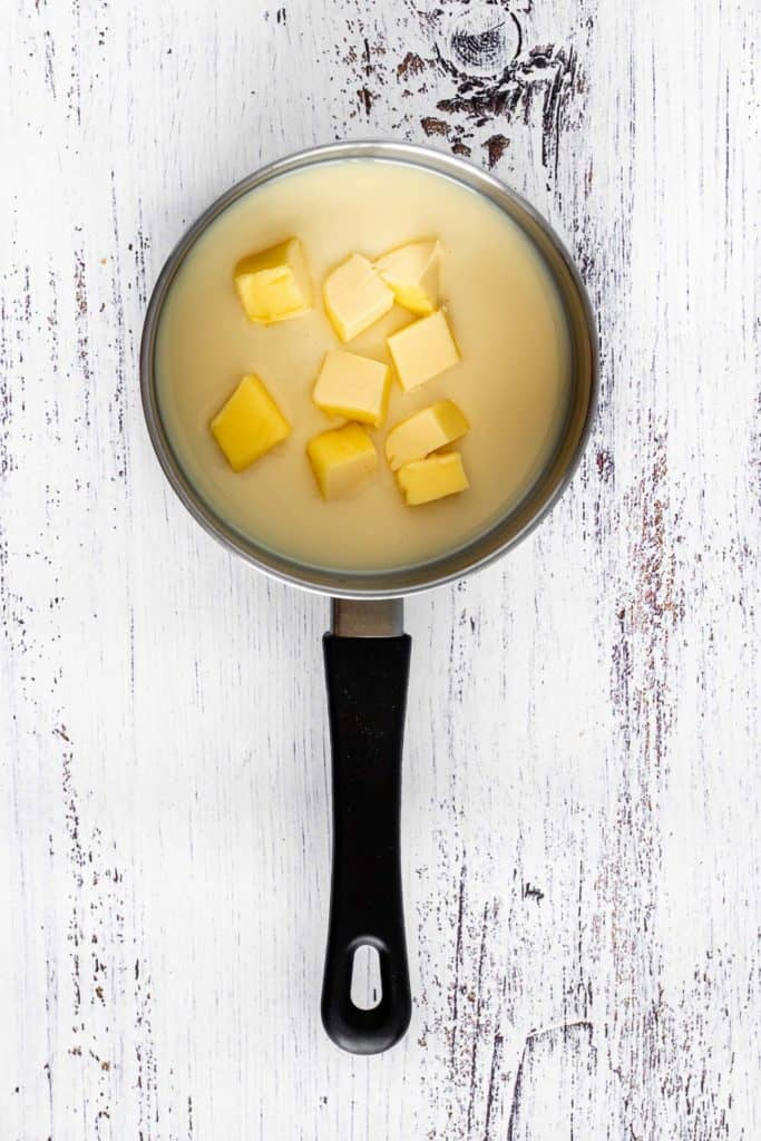 Small saucepan with condensed milk and butter cut into small cubes