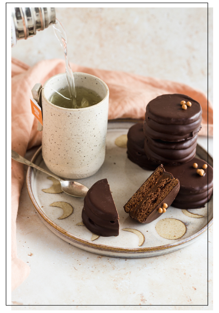 Dark chocolate alfajores on a plate with a cup of tea