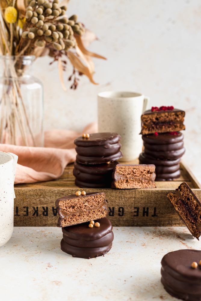 Dark chocolate alfajores on a wooden tray, with some dried flowers at the back and a ceramic mug