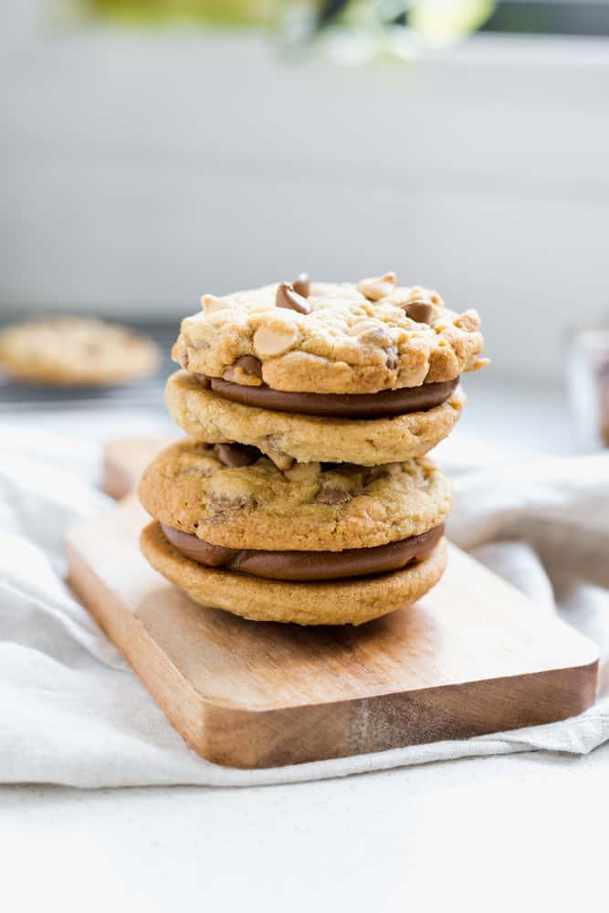 two chocolate chip cookies alfajores filled with dulce de leche on a wooden board